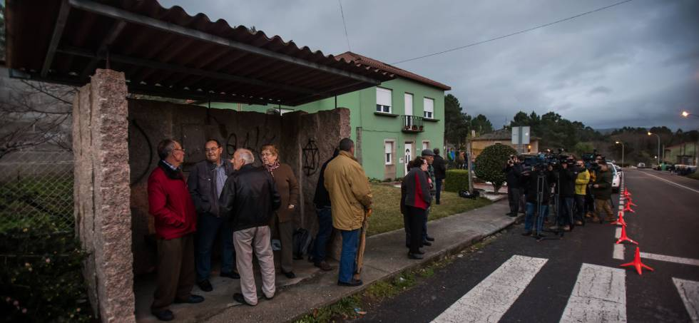 Vecinos de Tarago (Rianxo), observan desde la parada del bus la casa del detenido por la desaparición de Diana Quer.