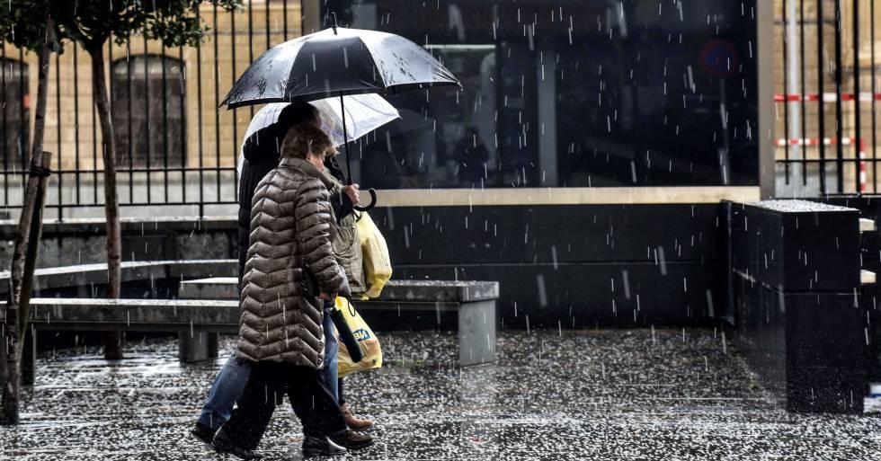 Dos personas se protegen de la intensa granizada caída en Bilbao el pasado diciembre.