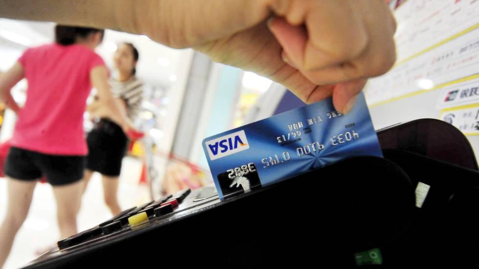 Un hombre paga con una tarjeta de crédito.