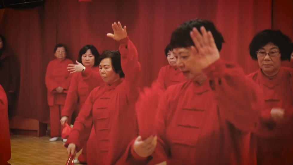 A group of Chinese seniors practices a traditional dance in the cultural center of Chinese New Year.