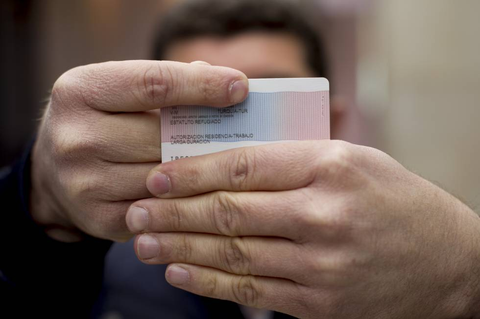 The first Turkish citizen granted political asylum in Spain shows his refugee ID card.