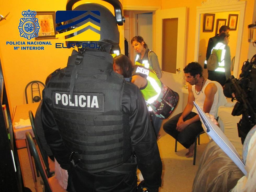 La policía en uno de los registros con uno de los 28 detenidos por tráfico de menores.