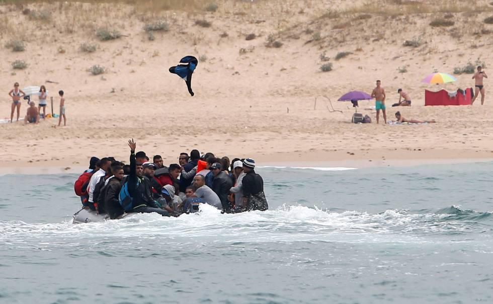 Migrantes saludan desde la embarcación en la que han cruzado el Estrecho hasta Tarifa, el 27 de julio.