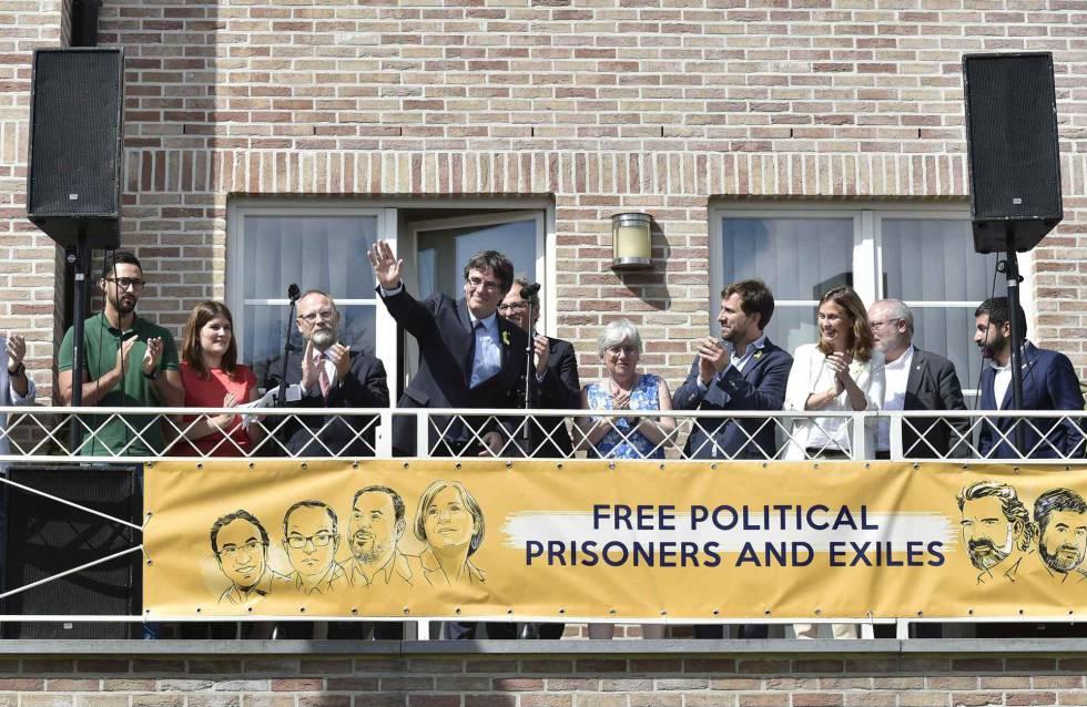 Puigdemont saluda desde el balcón de su residencia en Waterloo.