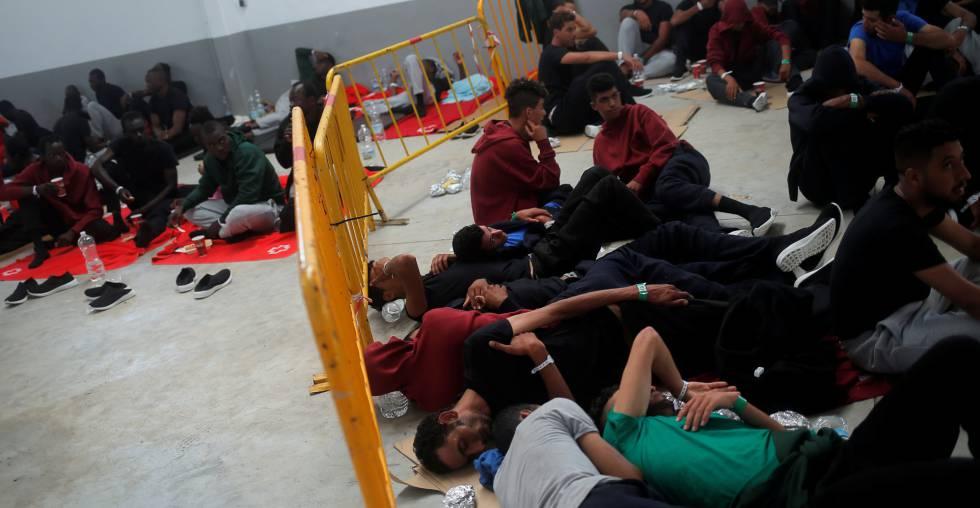 Un grupo de migrantes interceptados en el Estrecho de Gibraltar esperan en una nave del puerto de Barbate (Cádiz) el pasado sábado.