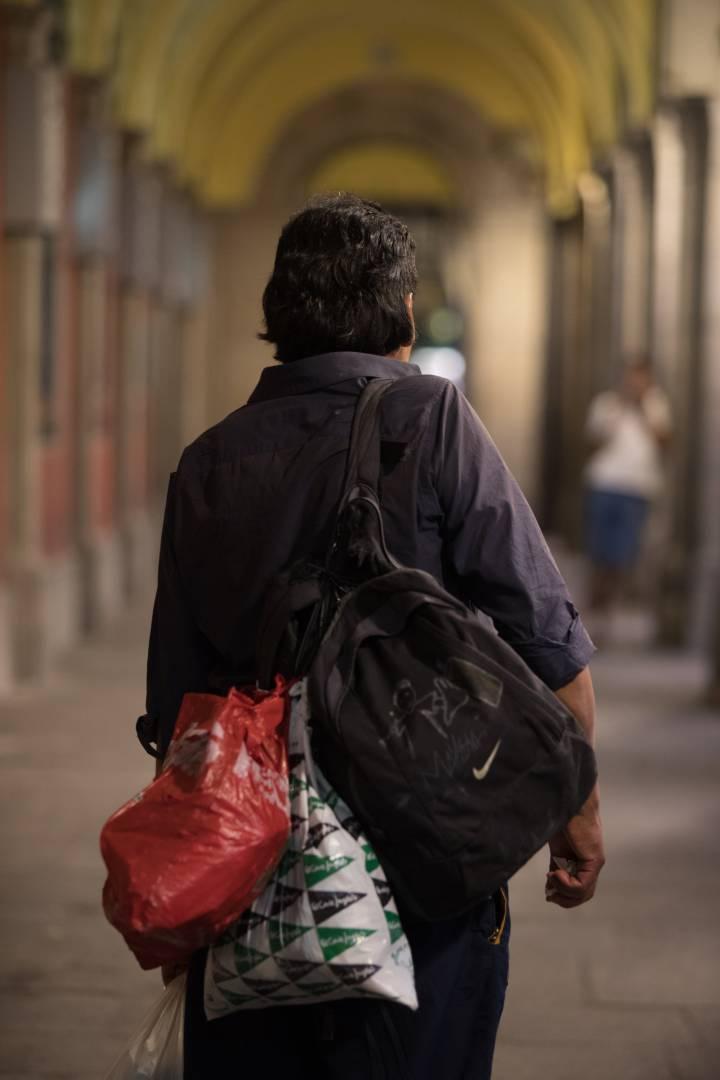 Raúl posa com seus pertences nos pórticos da Plaza Mayor. Fotografia: Víctor Sainz