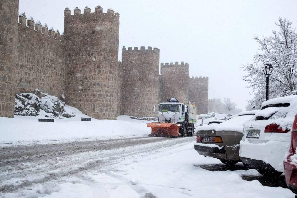 Una máquina quitanieves trabaja para retirar la nieve caída junto a la muralla de Ávila el pasado mes de marzo.  rn