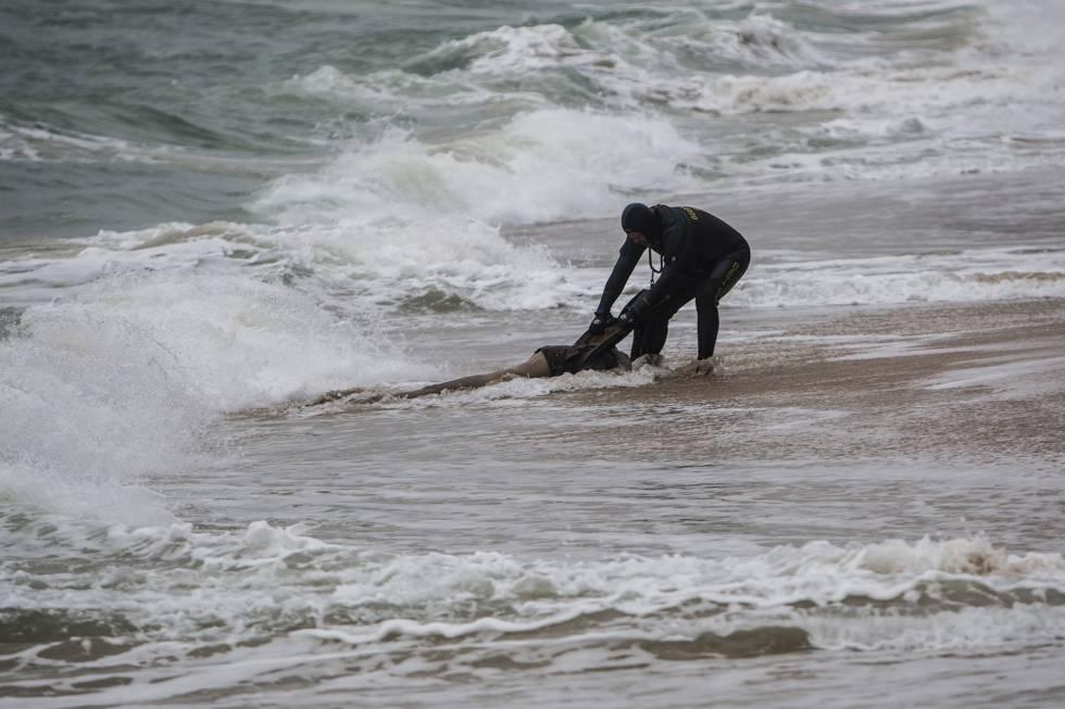 Un agente de la Guardia Civil rescata el cadáver de un inmigrante el pasado jueves en una playa de Caños de Meca en Cádiz.