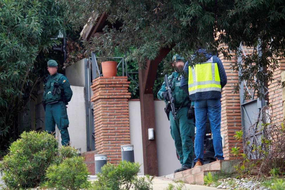 Agentes en la puerta de una casa durante un registro en la calle Fuelle de Sotogrande (Cádiz).
