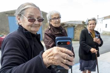 Três vizinhos mostram o celular com o botão vermelho de emergência.