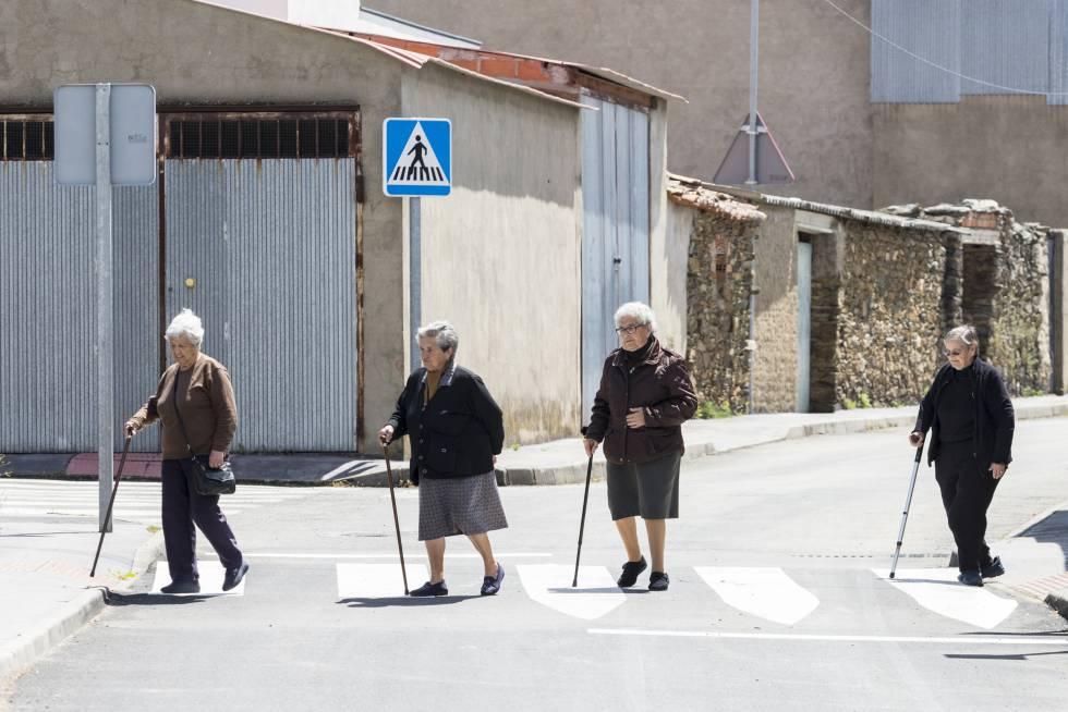 Quatro vizinhos andam por uma das ruas de Pescueza.