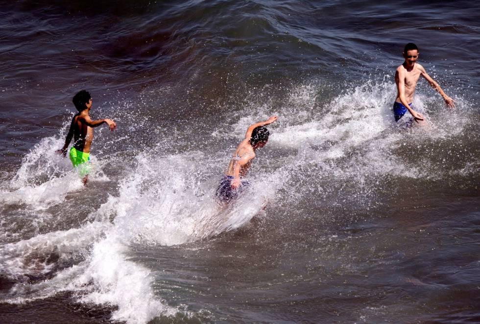 Unos jóvenes se bañan en la playa del Rincón de la Victoria (Málaga).