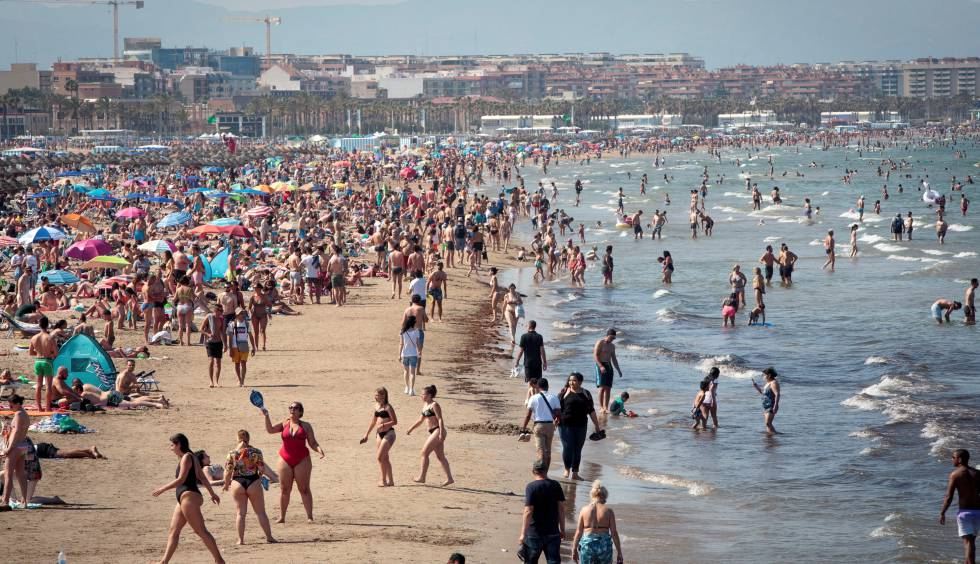 Miles de personas disfrutan este sábado de las altas temperaturas en la playa de la Malvarrosa de Valencia.