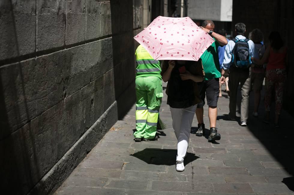 Turistas pasean bajo las altas temperaturas por el centro de Barcelona.
