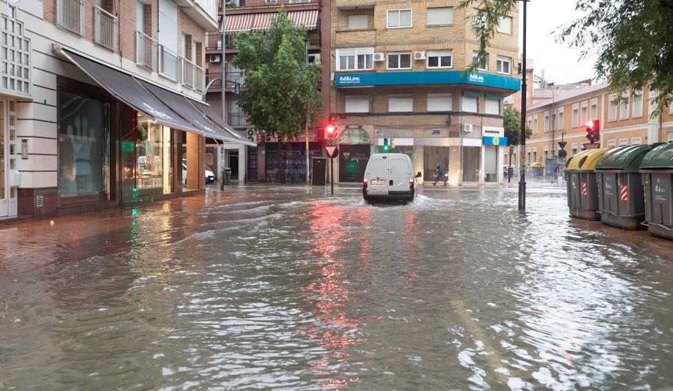 Un coche circula esta mañana por la calle Princesa de Murcia, inundada tras las intensas lluvias.