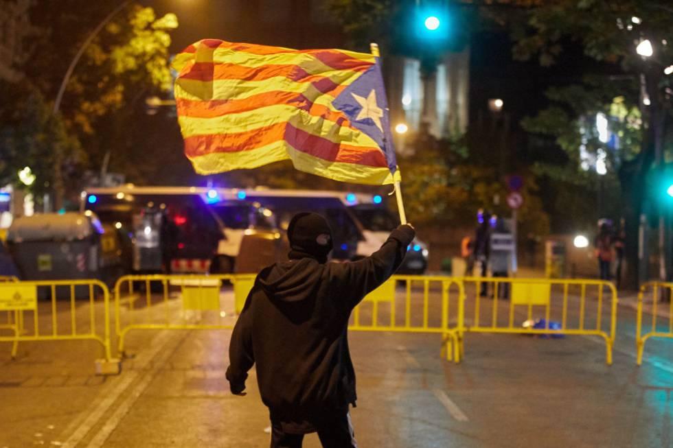 Un manifestante enmascarado porta una