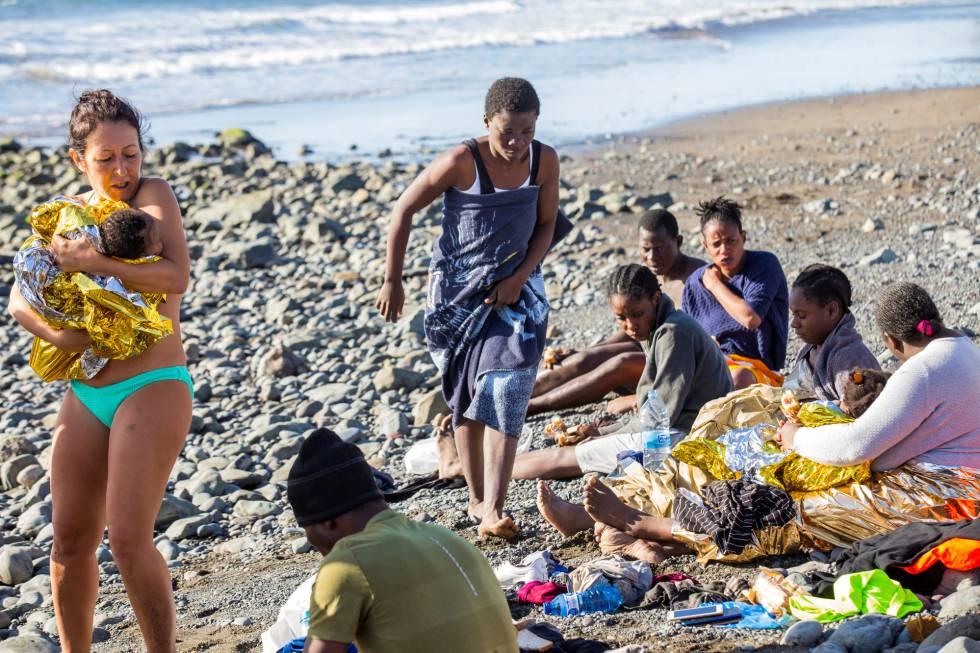 Una bañista sostiene en brazos a un bebé que llegó en patera a la playa del Águila (Gran Canaria).