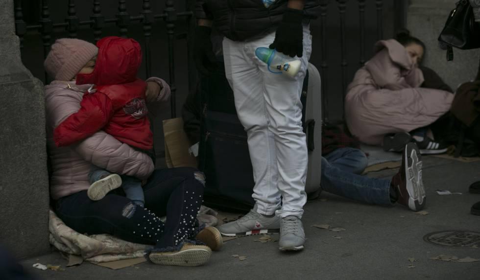 Un grupo de solicitantes de asilo aguarda frente al Samur Social, en Madrid, un plaza de acogida ante el colapso de la red nacional.