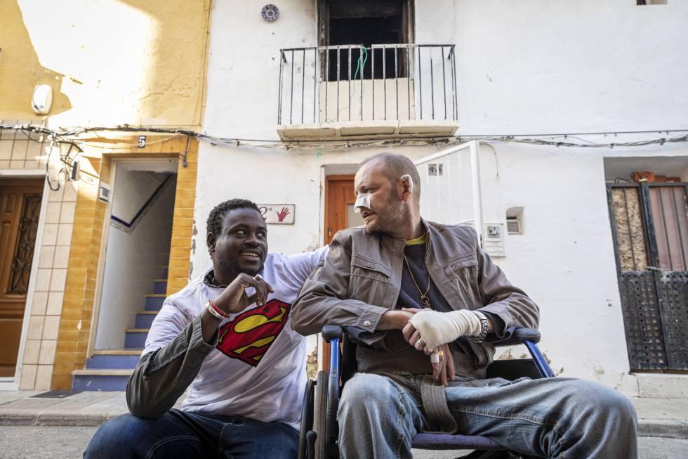 El senegalés Gorgui Lamine Sow y el hombre al que salvó Alex Caudeli, este martes, frente a la casa incendiada.