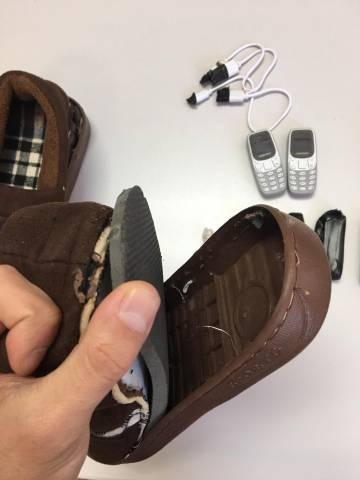 Suela de una zapatilla en la que se ocultaban los dos miniteléfonos que aparecen en la imagen y que fueron requisados por funcionarios de prisiones.