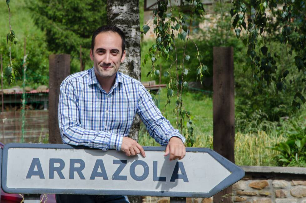 Juan Francisco Arrazola, sobre el panel que dirige a la antigua localidad de Arrazola, integrada ahora en el municipio de Atxondo (Vizcaya).