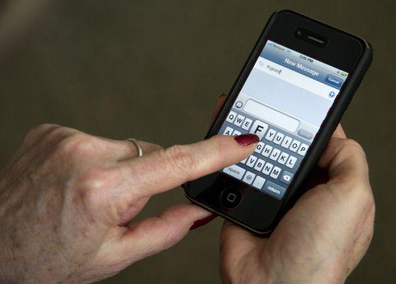 Una mujer usa su Iphone.