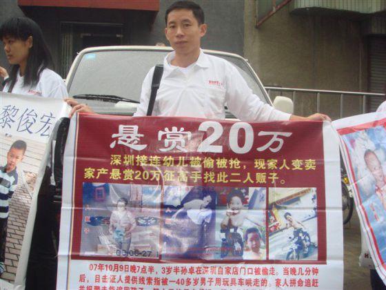 5fb1eb965c Un ciudadano chino sostiene un cartel con fotos de niños desaparecidos