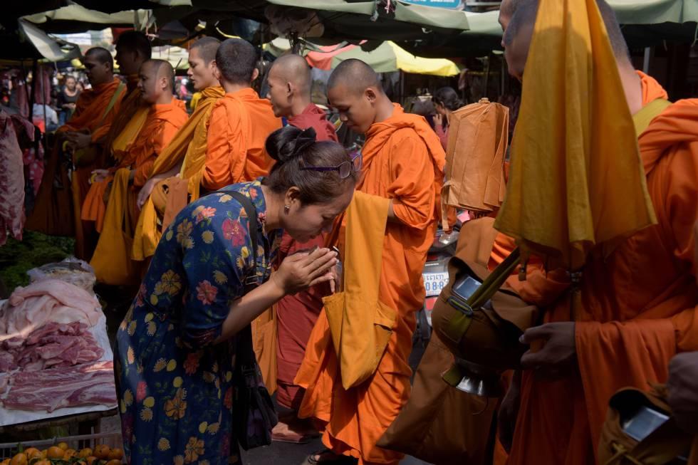 Una mujer frente a monjes budistas en Camboya.