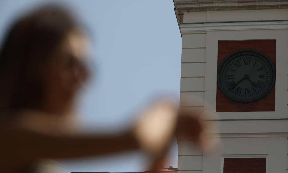 Un joven consulta la hora en la Puerta del Sol.