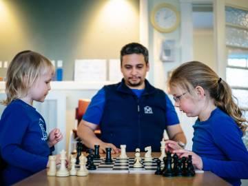 Dos niñas juegan al ajedrez en presencia del maestro.