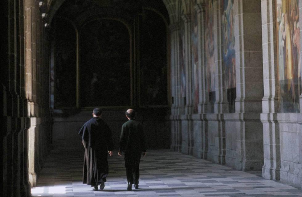 Dos monjes agustinos paseando por el claustro del monasterio de El Escorial.