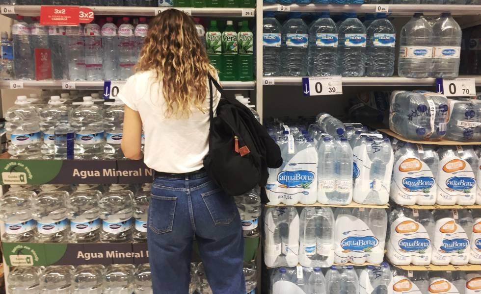 Una joven frente al estante de botellas de agua de plástico en un supermercado en Madrid.