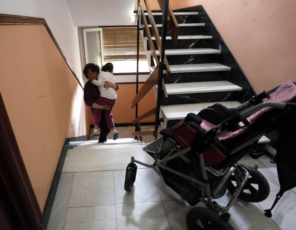 Una mujer sube en brazos a su hija con discapacidad a su casa en Madrid.