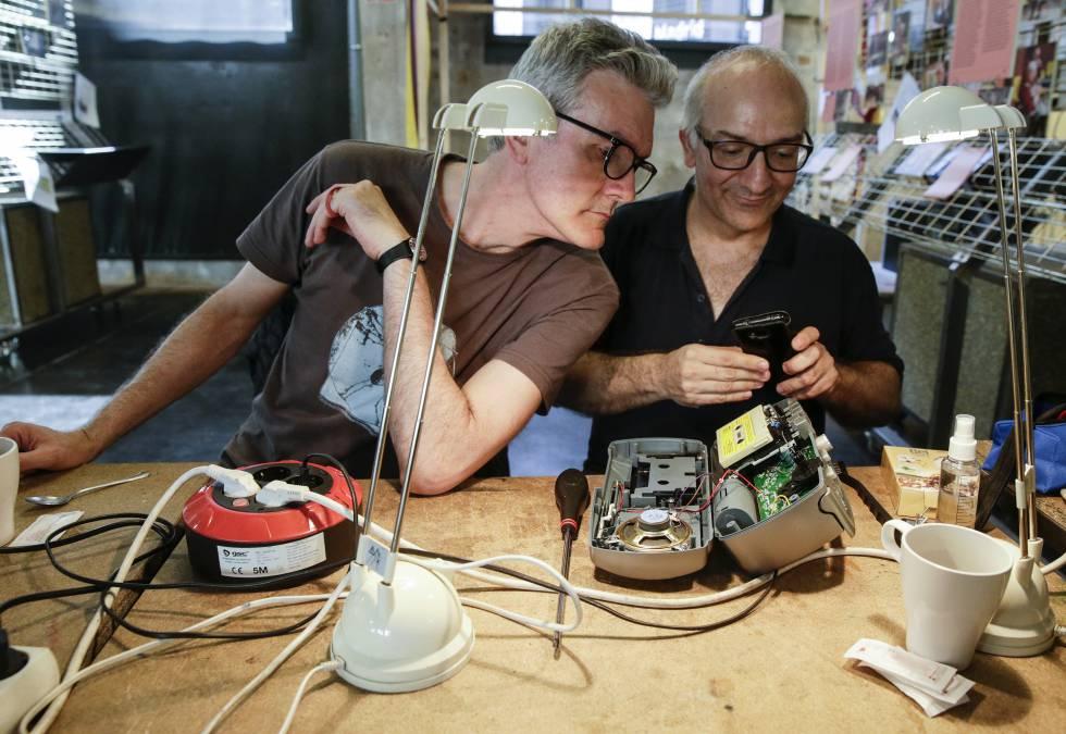 El reparador José Manuel Gutiérrez (derecha) junto a José Ramón Martín, otro voluntario, arreglan un radiocasete el pasado sábado en el Repair Café de MediaLab-Prado, en Atocha (Madrid).