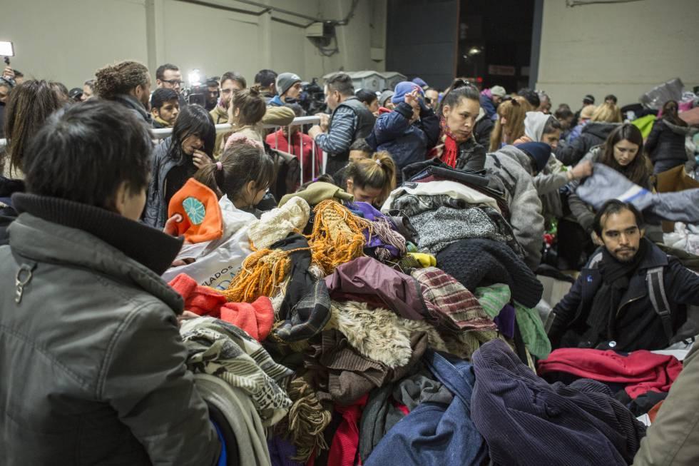 Personas en situación de calle buscan ropa con la que abrigarse entre las donaciones recibidas por River.