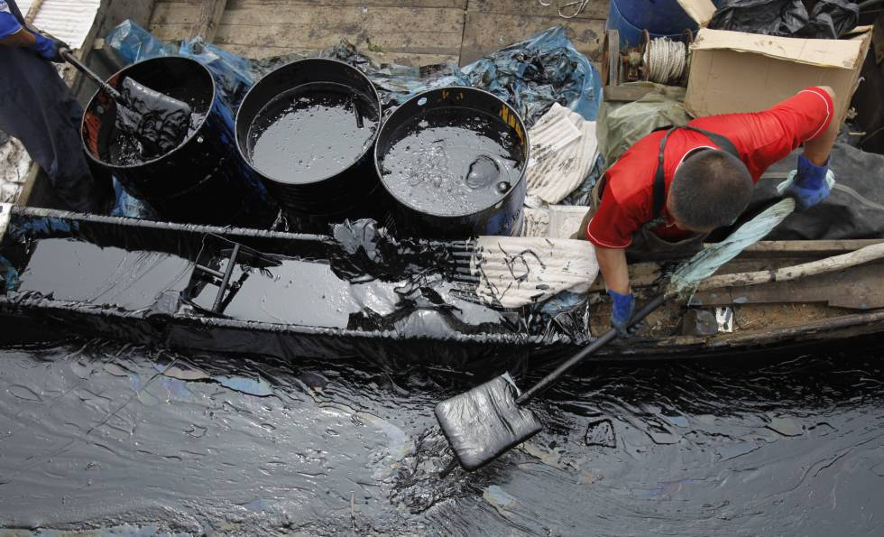 Un pescador recoge crudo en China tras un vertido en 2010.