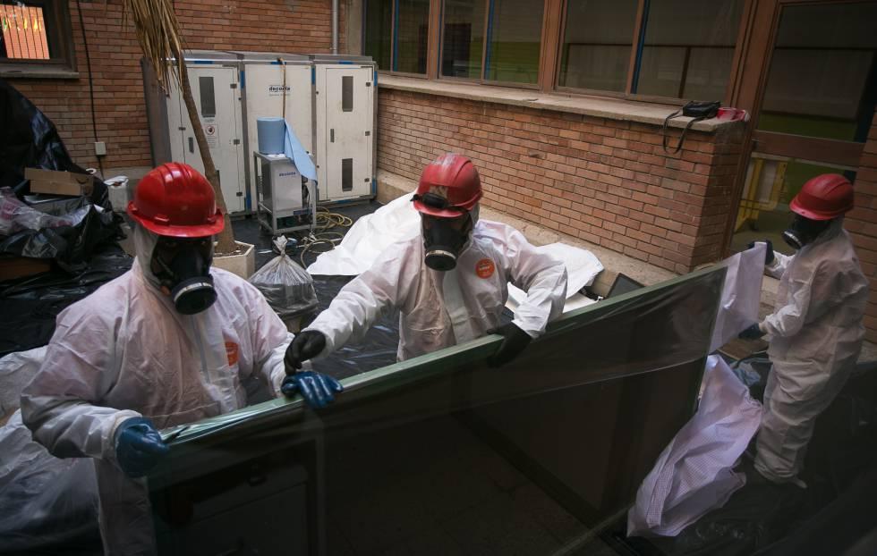 Trabajadores retiran una de las pizarras con amianto en un colegio de Cataluña.