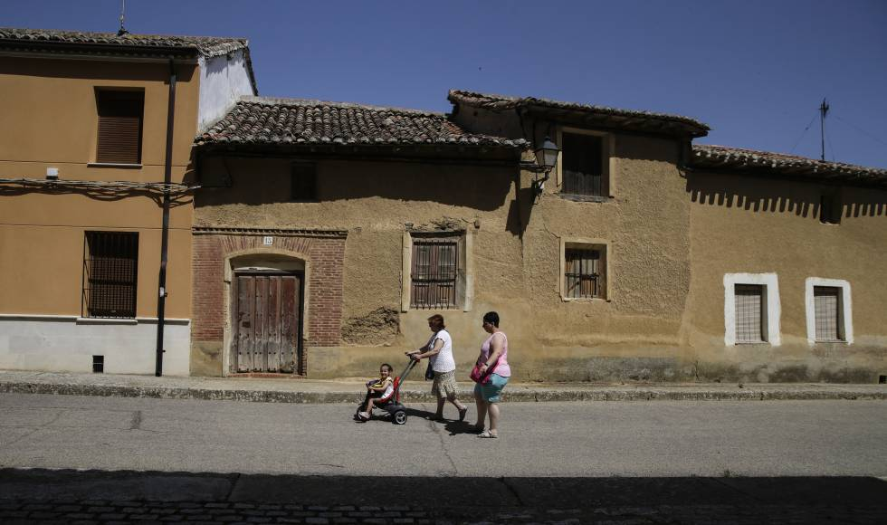 Dos mujeres pasean junto a una niña por Paredes de Nava.