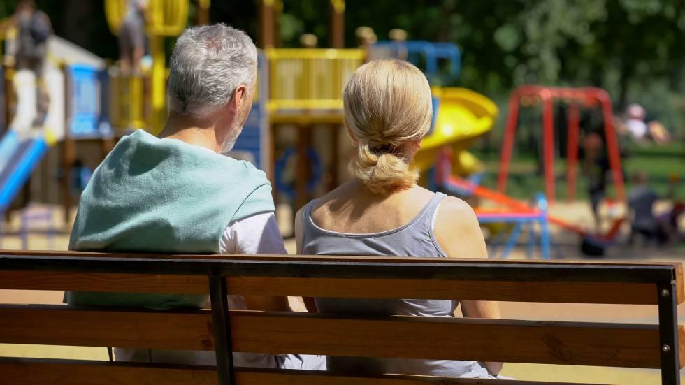 Una pareja observa a los niños en un parque.