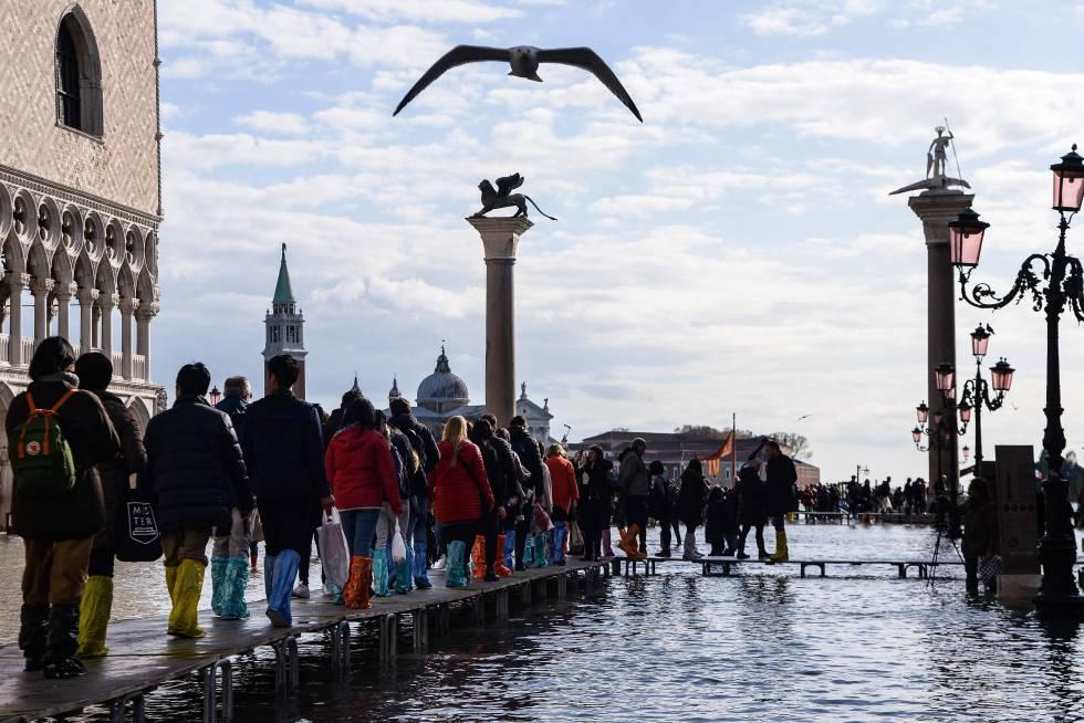 Varias personas caminan por la plaza de San Marcos de Venecia, completamente inundada.