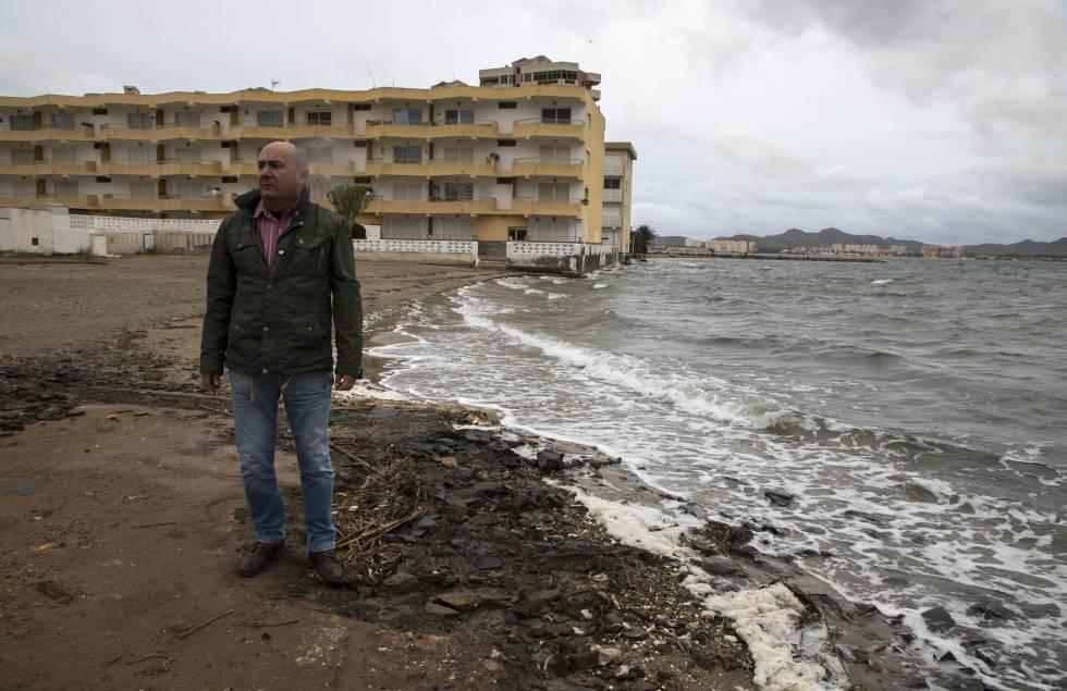 Javier Caballero posa junto al edificio en el que vive, al que ya ha llegado el Mar Menor.