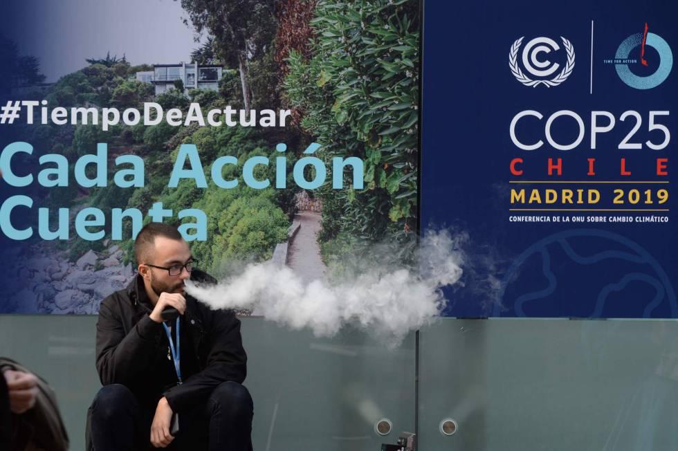 Un hombre fuma un cigarrillo electrónico en la entrada de la Cumbre del Clima que se celebra en Madrid.