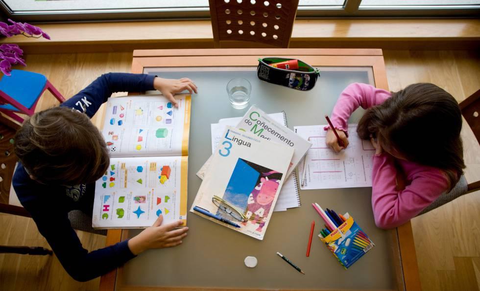 Unos niños hacen deberes con libros en gallego.
