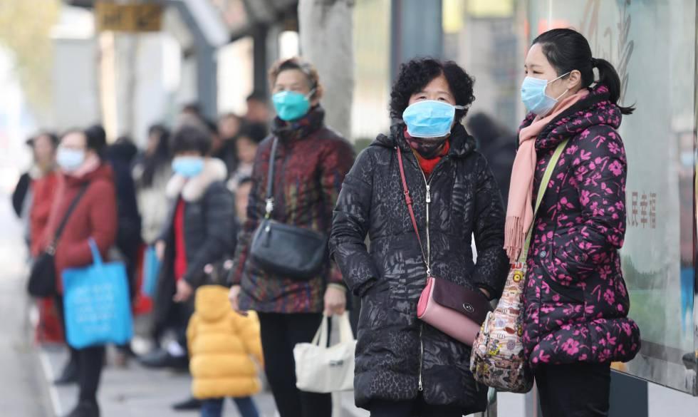 Vecinos de la localidad china de Wuhan se protegen con mascarillas.