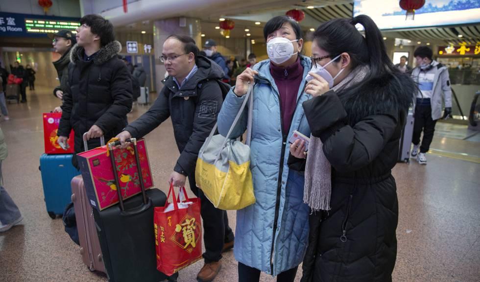 Un grupo de viajeros usa este martes mascarillas en una estación ferroviaria en Pekín.
