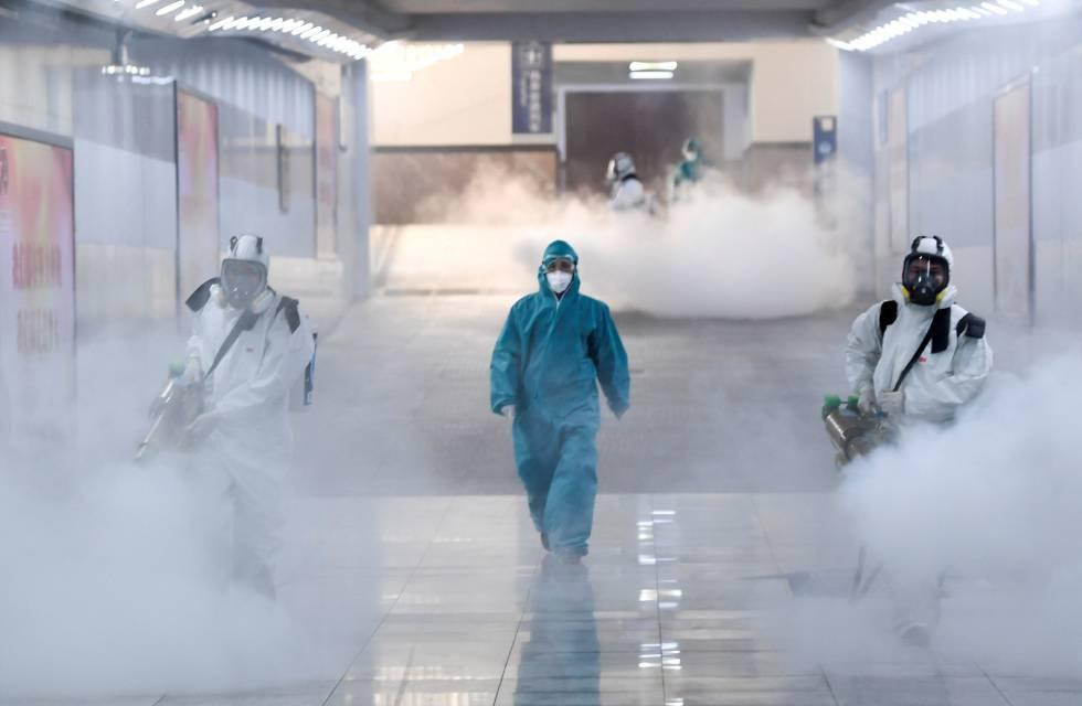 Voluntarios desinfectan una estación de tren en Changsha, provincia de Hunan.