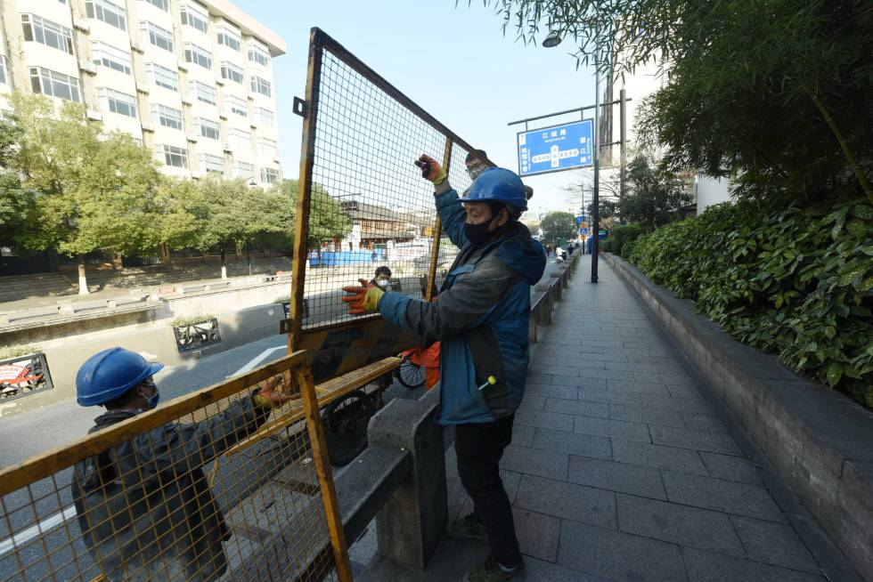 Trabajadores de Hangzhou instalan vallas en las carreteras para impedir la movilidad y hacer frente a la expansión del coronavirus.
