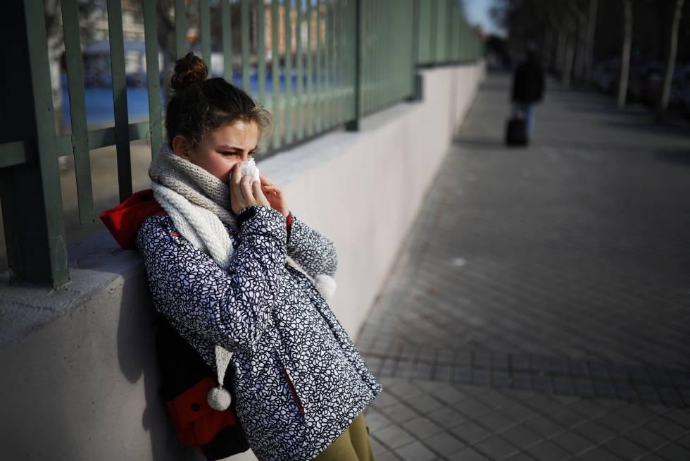 Una niña se suena los mocos a la salida de su colegio en Madrid.