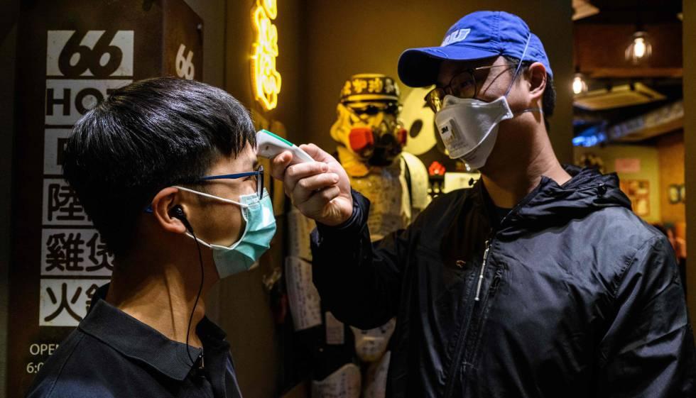 Un hombre le toma la temperatura a otro en Hong Kong.