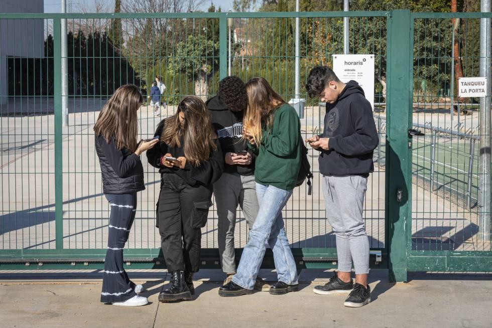 Adolescentes, en la puerta de un centro escolar en Valencia, con sus móviles.